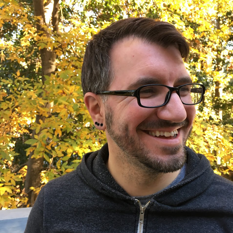 Headshot of Bret with autumn foliage in the background