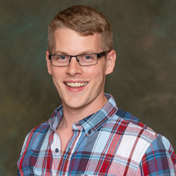 Headshot of Andy with a gray background. He has a plaid shirt on and is swearing glasses and smiling.